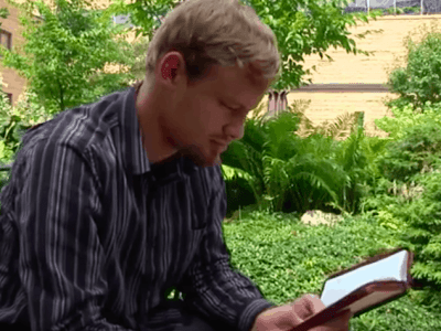 man seated in a garden reading a bible