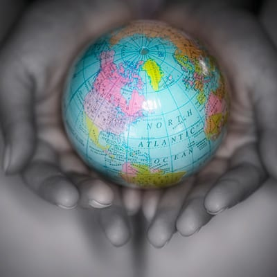 small globe held in cupped hands